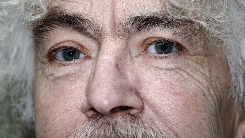 Gesichtsausschnitt eines alten Mannes mit grauen Locken und Schnurrbart