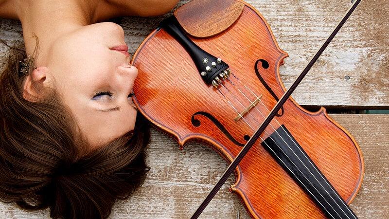 Junge Frau liegt auf Boden, daneben Geige