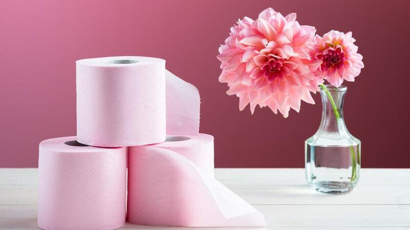 Drei rollen rosa Toilettenpapier neben Blume auf einem Tisch