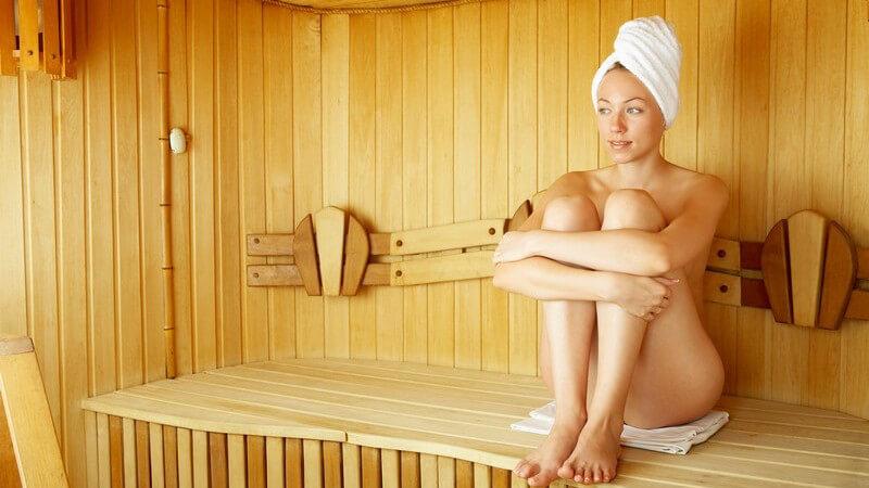 Nackte Frau mit Handtuch auf Kopf sitzt in Sauna auf Bank