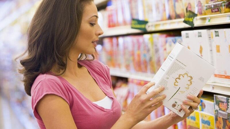 Dunkelhaarige Frau steht vor Regal beim Einkauf im Supermarkt