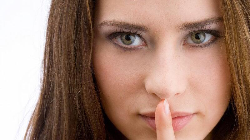 Gesichtsportrait, junge Frau hält Zeigefinger vor geschlossenen Mund