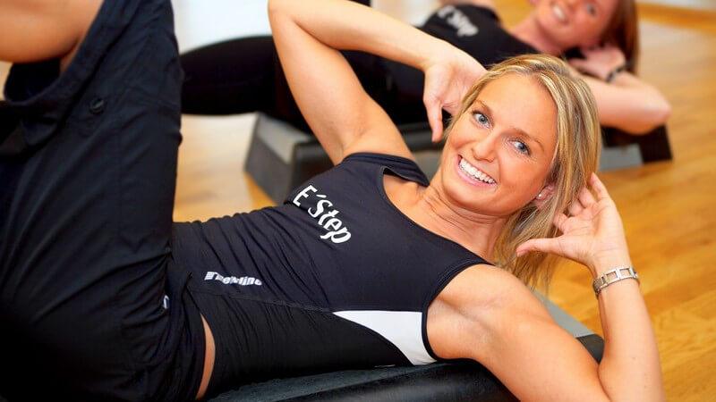 Zwei lächelnde Frauen machen Sit-Ups im Aerobicraum