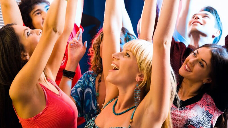 Gruppe junger Leute auf Party hebt Arme beim Tanzen