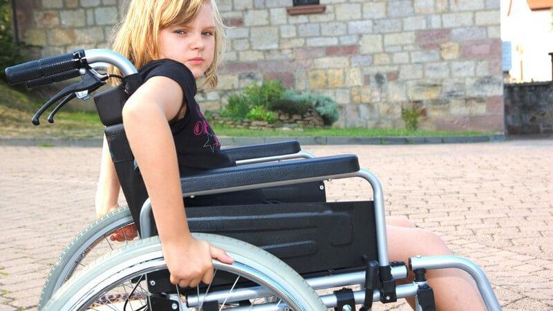 Kleines Mädchen im Rollstuhl schaut traurig in Kamera
