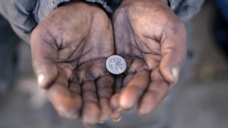 Offene Hände eines Bettlers, darin liegt eine Münze