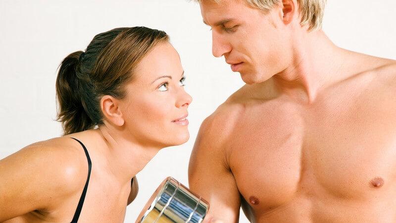 Frau und Mann beim Krafttraining, sie schauen sich an, er mit nacktem Oberkörper und Hantel
