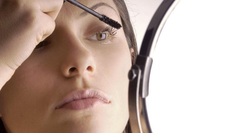 Frau vor Kosmetikspiegel trägt Mascara auf, weißer Hintergrund