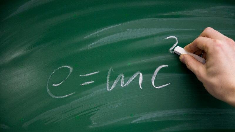 Rechte Hand eines Lehrers schreibt mit Kreide Relativitätstheorie bzw. Formel an Tafel