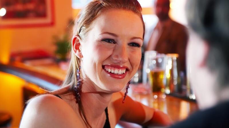 Frau mit hochgestecktem Pony lächelt Gesprächspartner an, sitzt an orangener Bar