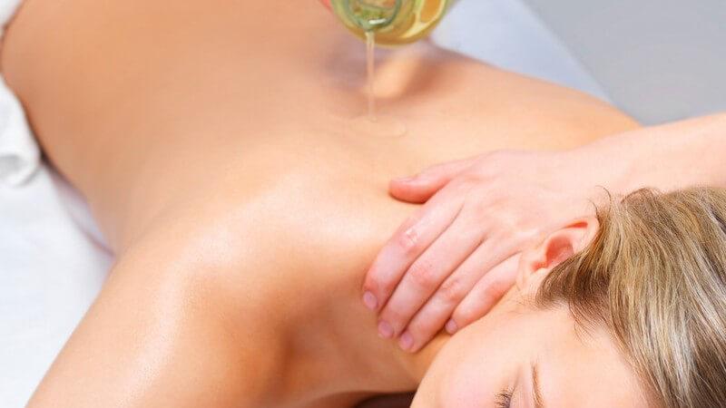 Junge Frau bekommt Massageöl auf den Rücken aufgetragen