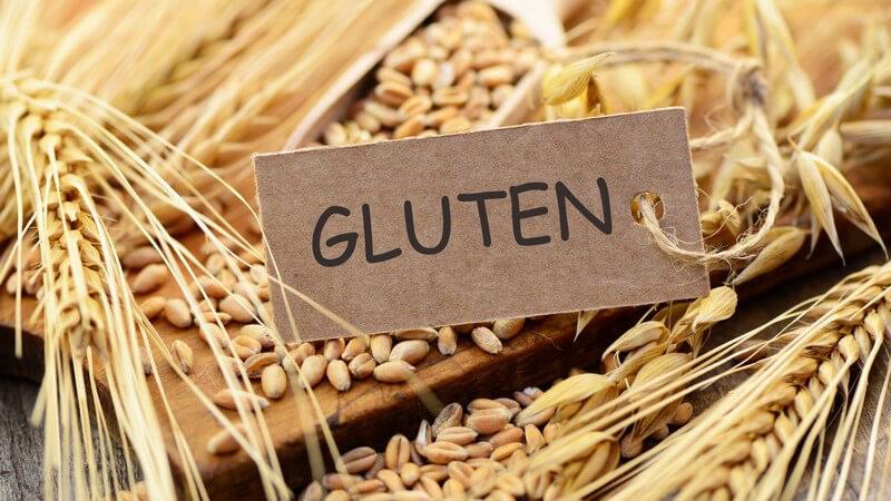 """Papierschild mit der Aufschrift """"Gluten"""" auf einem Haufen Weizenähren und -körner"""
