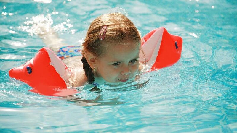 Kleines Mädchen mit Schwimmflügeln im Wasser