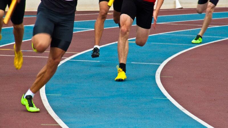 Beine von Leichtathleten, Sportlern, die auf einer Laufbahn laufen