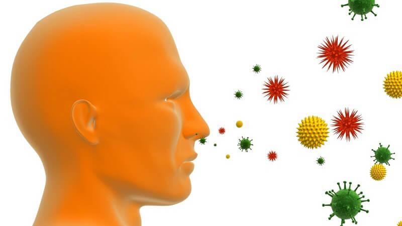 Grafik Seitenansicht menschlicher Kopf, vor ihm fliegen bunte Kugeln - Pollenallergie