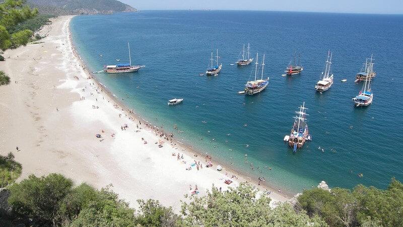 Boote auf blau-türkisem Meer vor weißem Strand, im Hintergrund Berge