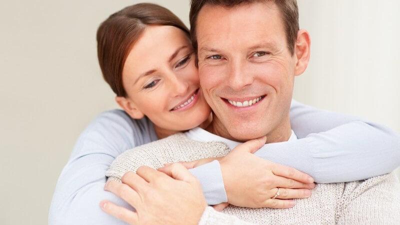 Frau umarmt ihren Mann von hinten, beide lächeln