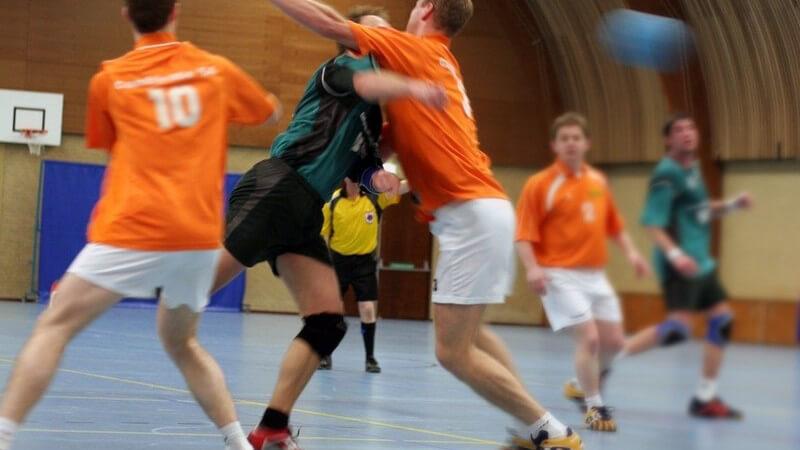 Handballspiel in Turnhalle, zwei Mannschaften, Zusammenstoß von zwei Spielern, Handball rechts im Bild