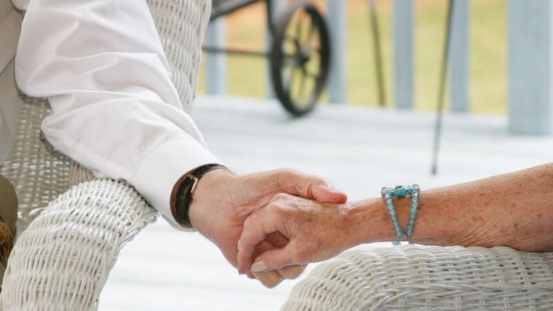 Nahaufnahme die beiden Hände eines älteren Paares halten sich