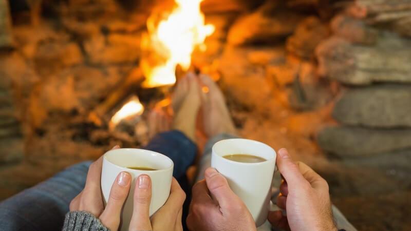 Kaminfeuer im Hintergrund, davor Hände eines Paars mit Kaffeebechern
