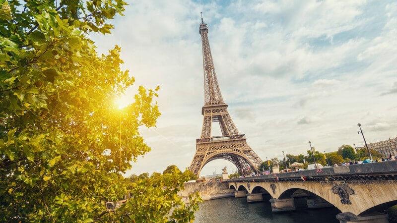 Grüner Baum, Eiffelturm und Brücke über die Seine bei Sonnenuntergang in Paris