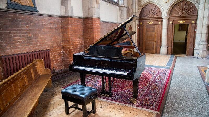 Schwarzes Klavier steht auf einem roten Teppich in einer katholischen Kirche