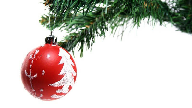 Rote Christbaumkugel an Weihnachtsbaum auf weißem Hintergrund