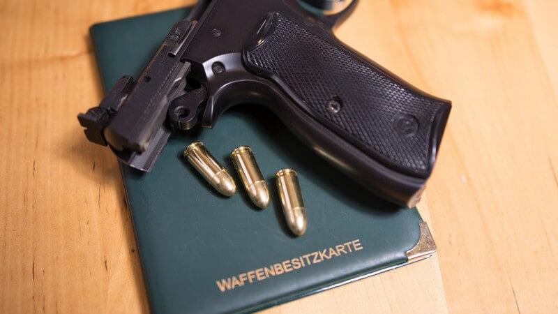 Pistole und drei Patronen liegen auf einer Waffenbesitzkarte
