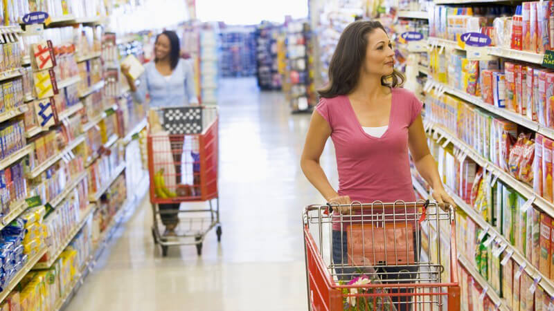 Zwei Frauen mit Einkaufswagen stehen an Regalen im Supermarkt