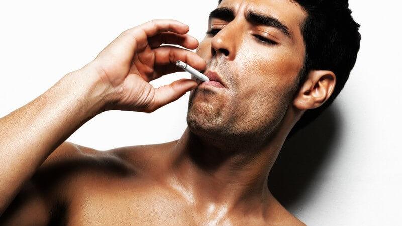 Mann mit nacktem Oberkörper an Wand gelehnt raucht, Macho