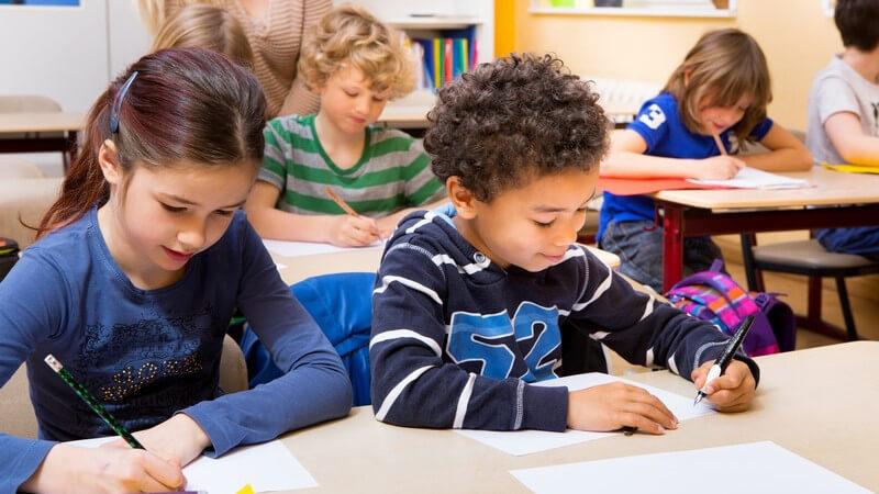 Grundschüler sitzen im Klassenzimmer und schreiben einen Test