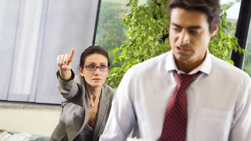 Geschäftsmann mit Akten verlässt verärgert den Raum, im Hintergrund Chefin, zeigt zur Tür
