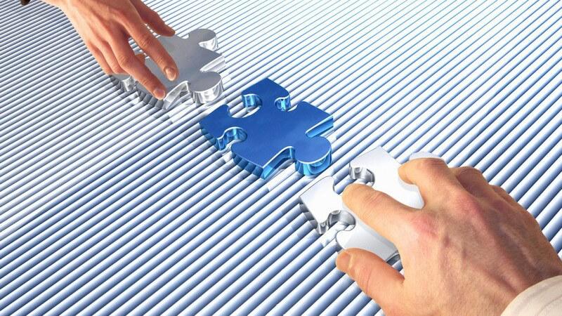 Zwei Hände (Frau und Mann) setzen Puzzleteile zusammen, Businessplan