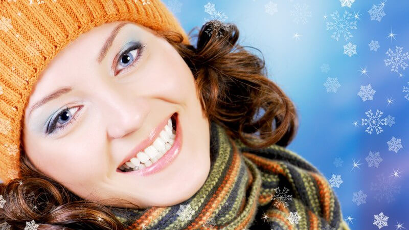 Junge dunkelhaarige Frau mit Wollmütze und Schal lacht in Kamera, im Hintergrund grafische Schneeflocken