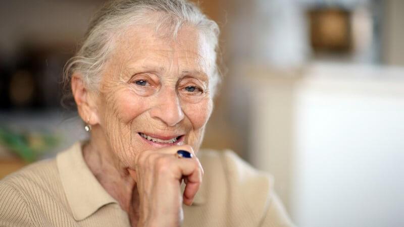 Alte Dame lächelt, das Kinn auf die rechte Hand gestützt, blauen Ring am Ringfinger