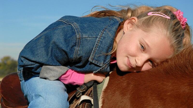 Blondes Mädchen in Jeansjacke sitzt auf braunem Pferd, den Kopf auf dessen Rücken gelegt