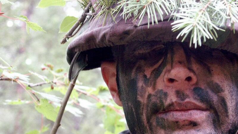 Gesicht eines Soldates, mit Helm und Tarnfarben