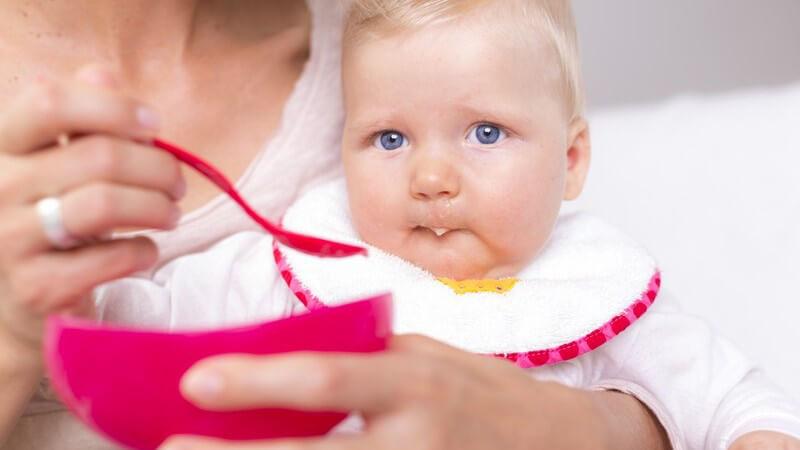 Blondes Baby mit Lätzchen wird mit Babybrei aus pinker Schale gefüttert
