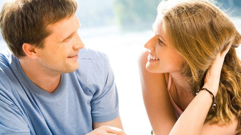 Paar ist draussen, sie schauen sich gegenseitig an und lächeln