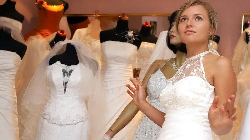 Junge Frau in Brautkleid mit Spitze in Brautmodengeschäft mit Schaufensterpuppe in Hintergrund