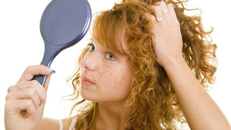 Junge Frau mit roten Locken und Sommersprossen schaut in Handspiegel und formt Haare