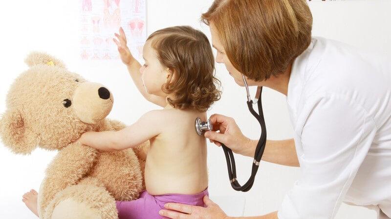 Kinderärztin hört ein Kleinkind mit einem Stethoskop am Rücken ab, das Kind hält einen großen Teddy