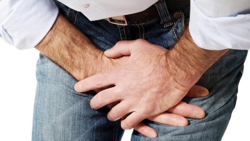 Mann in Jeans und Hemd fasst sich vor Schmerzen gekrümmt in den Schritt