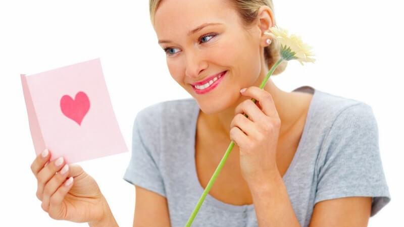 Frau hält Blume in Hand und schaut sich Valentinskarte an