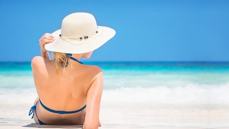 Junge Frau liegt in blauem Bikini und mit weißem Sonnenhut im Sand am Meer