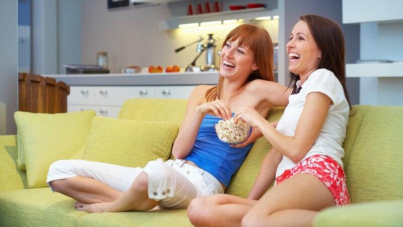 Zwei Frauen sitzen in Wohnung in Wohnzimmer auf Sofa, essen Popcorn, lachend, schauen Fernsehen oder Filme