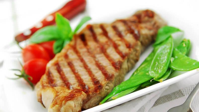 Gegrilltes Steak auf weißem Teller mit Salat und Tomaten