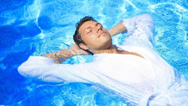 Junger Mann liegt auf Rücken im Pool, trägt weißen Bademantel