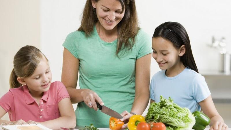 Zwei Mädchen schauen einer Frau beim Gemüseschneiden zu