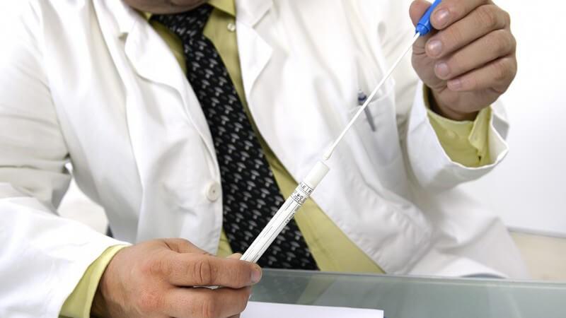 Laborant in weißem Kittel und Krawatte sitzt am Tisch und hält ein Abstrichröhrchen zur DNA-Analyse in den Händen